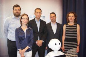Csapatunk tagjai és természetesen Pepper a humanoid robot, aki kicsit elvarázsolt módon kifele fordult. A digitalizált ügyfélkiszolgálás szakértői vagyunk.