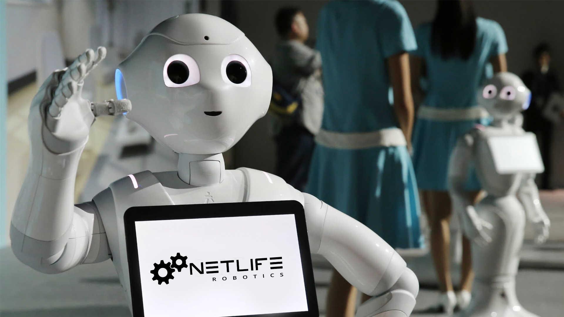 Pepper, a humanoid robot, a háttérben pedig kék ruhás nők, és egy másik robot látható.